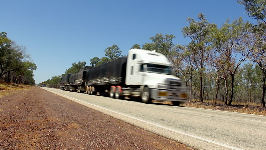 Big trucks with three trailers passing by empty road in Outback Australia. Desert freeway flanked by trees. Long distance goods transportation, driver profession concepts Royalty-Free Stock Footage #1015759264