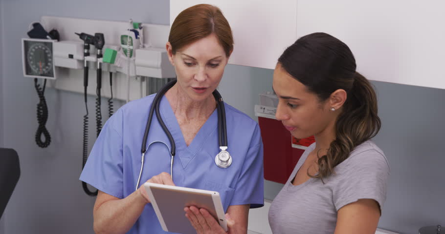 Portrait of middle aged female nurse using tablet computer to show young latina patient her medical test results. Close up of nurse explaining to young hispanic patient her health condition | Shutterstock HD Video #1015761280