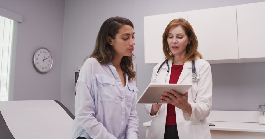 Lovely young hispanic woman looking at test results on tablet computer with senior doctor. Mid aged medical doctor using portable tablet to review health history of patient