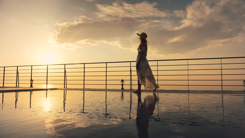 Slow motion - Beautiful shot of a woman in a long flow dress walking by the poolside and splashing water with her foot at colorful sunset. Girl leaning on the railing to enjoy the view at end of clip #1015761727