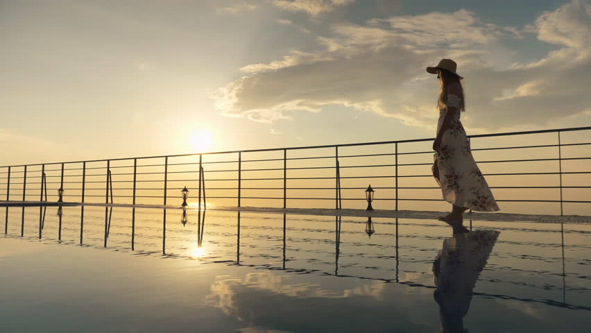 Slow motion - Beautiful shot of a woman in a long flow dress walking by the poolside and splashing water with her foot at colorful sunset. Girl enjoying summer vacation at luxury villa Royalty-Free Stock Footage #1015762348