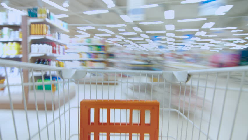 Time Lapse of the Shopping Cart Moving Between Various Aisles and Section in the Big Supermarket. Inside Trolley Various Healthy Items and Convenience Food. Shot on RED EPIC-W 8K Helium Cinema Camera.