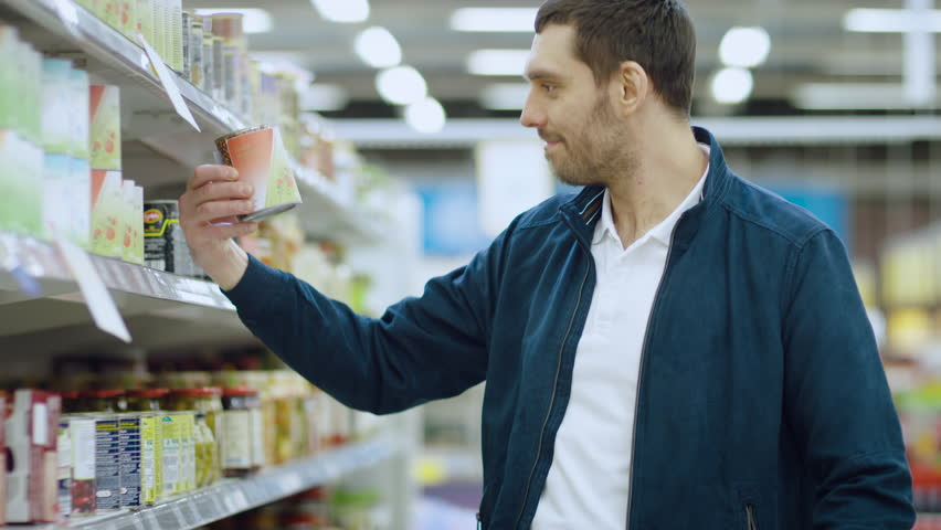 At the Supermarket: Handsome Man Browses Through Shelf with Canned Goods, Places Tin Can into His Shopping Cart. Shot on RED EPIC-W 8K Helium Cinema Camera.