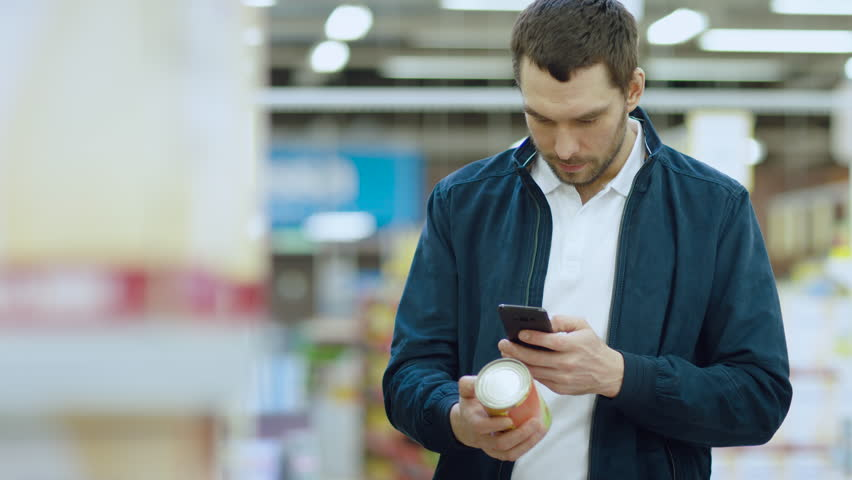 At the Supermarket: Handsome Man Uses Smartphone to Check Nutritional Value of the Canned Goods and Buy it. He's Standing with Shopping Cart in Canned Goods Section. Shot on RED EPIC-W 8K Camera.