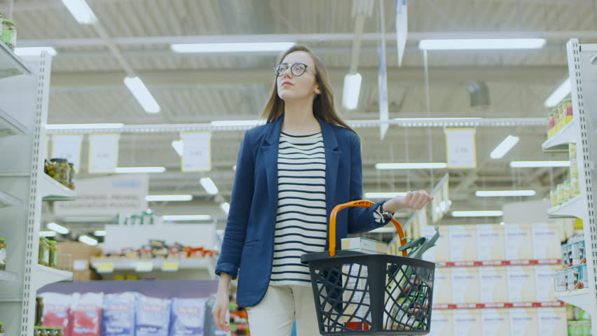 At the Supermarket: Beautiful Young woman with Shopping Basket Walks Through Canned Goods Section, Browsing. Big Store with Lots of Aisles. Shot on RED EPIC-W 8K Helium Cinema Camera.
