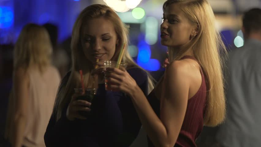 Seductive hot ladies drinking cocktails, moving sexy bodies to music at disco #1015782418