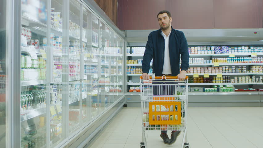At the Supermarket: Handsome Man Pushes Shopping Card and Browses for Products in the Frozen Goods Section. Other Customer in the Background. Shot on RED EPIC-W 8K Helium Cinema Camera.