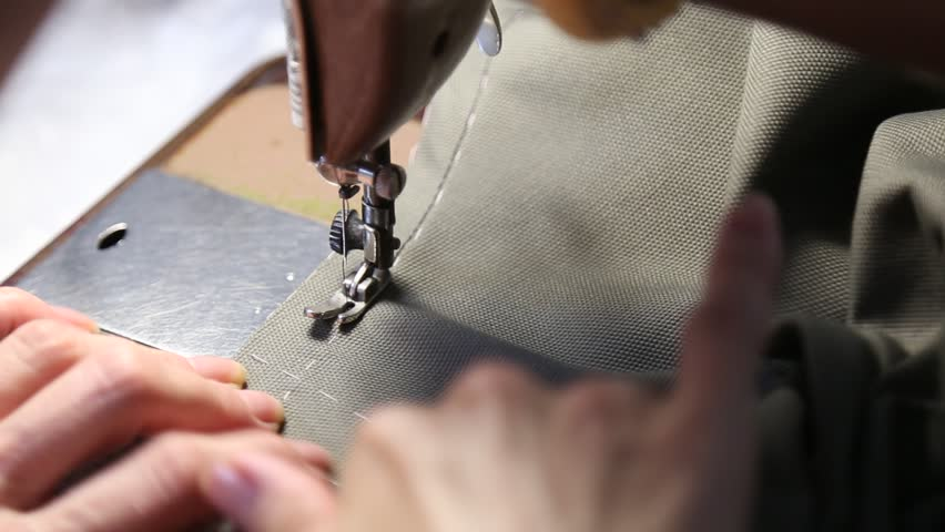 The tailor sews on the old vintage sewing machine. Women's hands behind her sewing.  | Shutterstock HD Video #1015786228