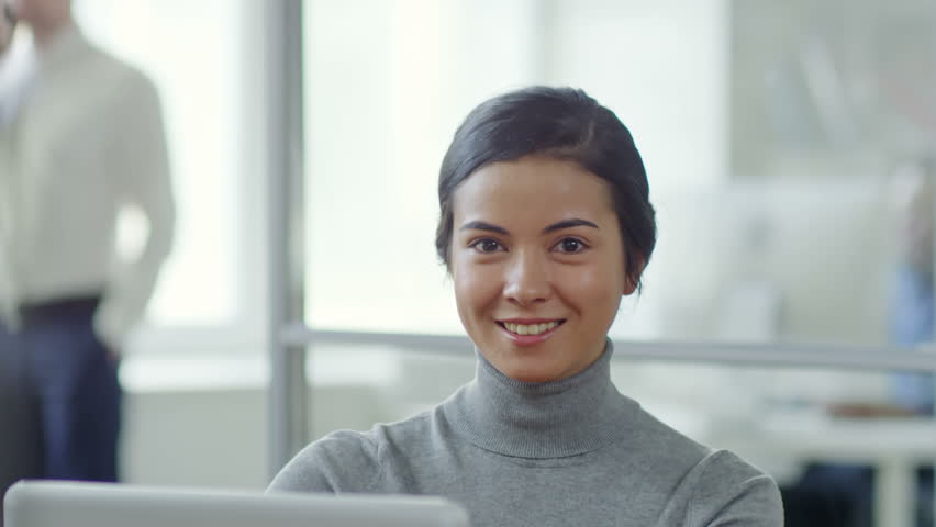 Tilt down shot of attractive young mixed race woman sitting at desk in office and working with laptop computer, then looking at camera and smiling | Shutterstock HD Video #1015794256