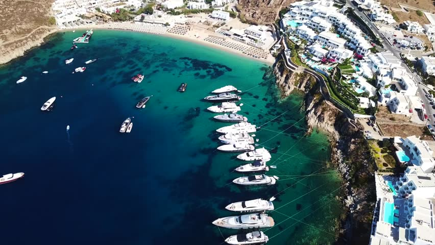 Aerial drone video of famous turquoise clear water beach of Psarou with luxury yachts docked in iconic island of Mykonos, Cyclades, Greece   Shutterstock HD Video #1015796179