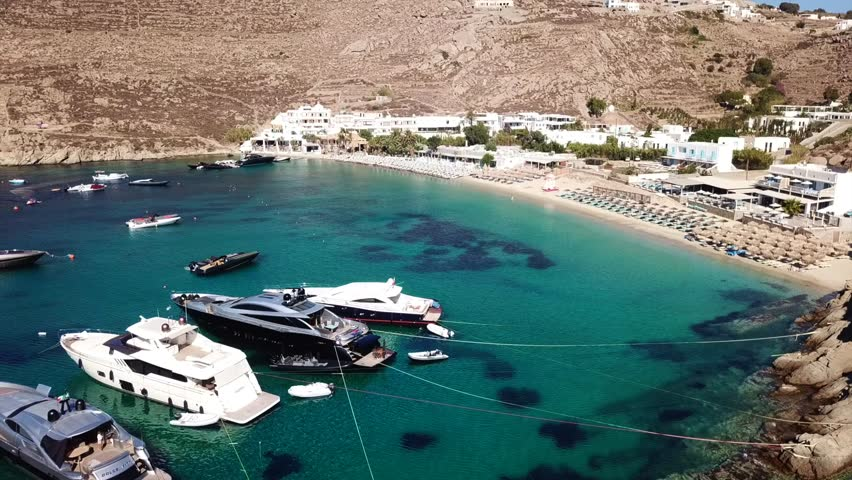 Aerial drone video of famous turquoise clear water beach of Psarou with luxury yachts docked in iconic island of Mykonos, Cyclades, Greece   Shutterstock HD Video #1015796200