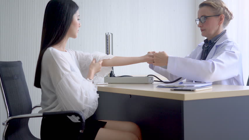 Senior female doctor checking blood pressure on a patient with sphygmomanometer in a medical room hospital.  | Shutterstock HD Video #1015802722
