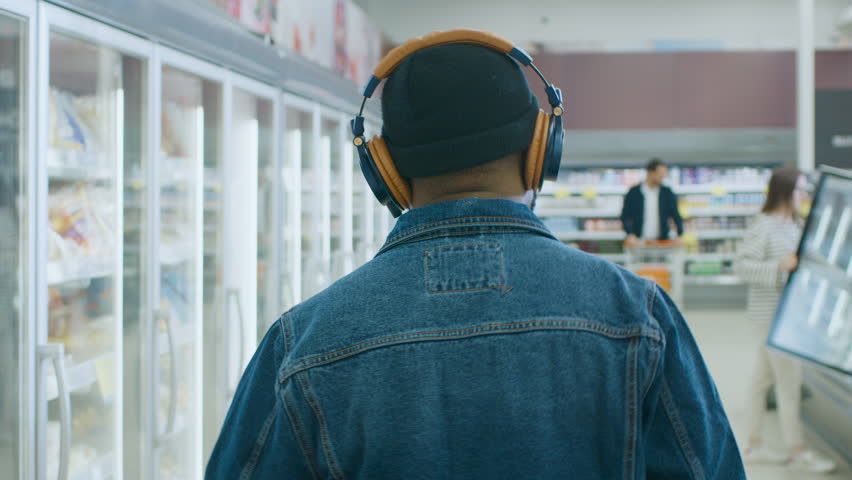At the Supermarket: Stylish African American Guy with Headphones Walks Through Frozen Goods Section of the Store. Following Back View Shot. Slow Motion. | Shutterstock HD Video #1015805038