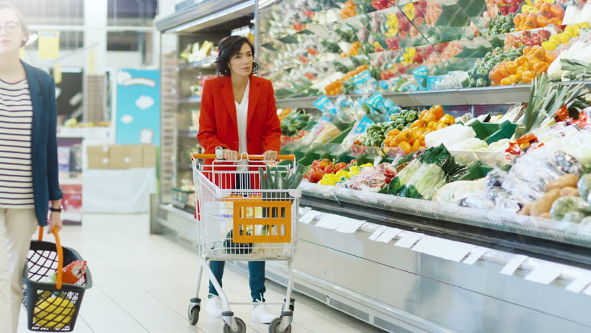 At the Supermarket: Beautiful Young Woman Walks Through Fresh Produce Section, Chooses Vegetables and Puts them in Her Shopping Cart. Shot on RED EPIC-W 8K Helium Cinema Camera.