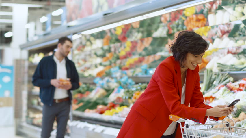 At the Supermarket: Beautiful Young Woman Uses Smartphone While Standing at the Fresh Produce Section of the Store. In the Background Other Customers Shopping. Shot on RED EPIC-W 8K Helium Camera. | Shutterstock HD Video #1015805287
