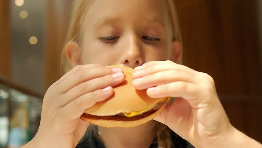 Beautiful happy hungry baby girl eating hamburger. Fast food concept. Tasty unhealthy burger sandwich in hands. | Shutterstock HD Video #1015834996