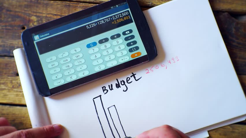 Economic settlement-business concept. men's hands,calculator,notebook and  marker on a wooden table.Close-up.Top view | Shutterstock HD Video #1015846222
