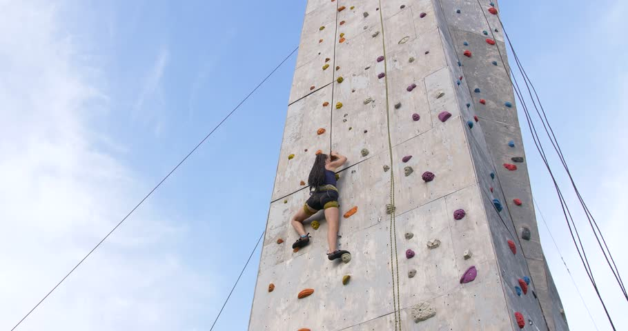 Boulder climber woman exercising at outdoor climbing gym wall. Training climbers on the climbing wall. Athletic girl has workout of rock-climbing in sport gym.