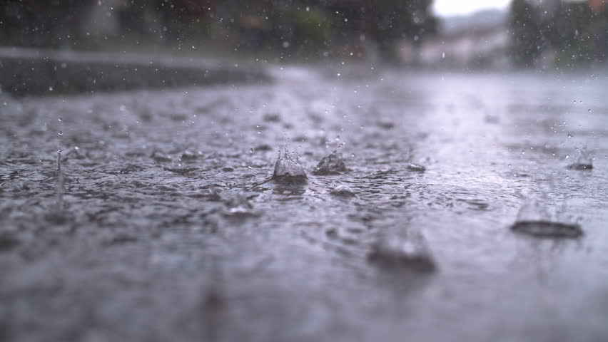 SLOW MOTION CLOSE UP: Autumn rain water drops falling into big puddle on asphalt, flooding the street. Road floods due to the heavy rain in wet season. Raindrops falling down onto submerged road | Shutterstock HD Video #1015854739