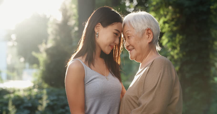 Happy asian grandmother and her granddaughter standing in park, hugging each other and smiling - portrait shot 4k