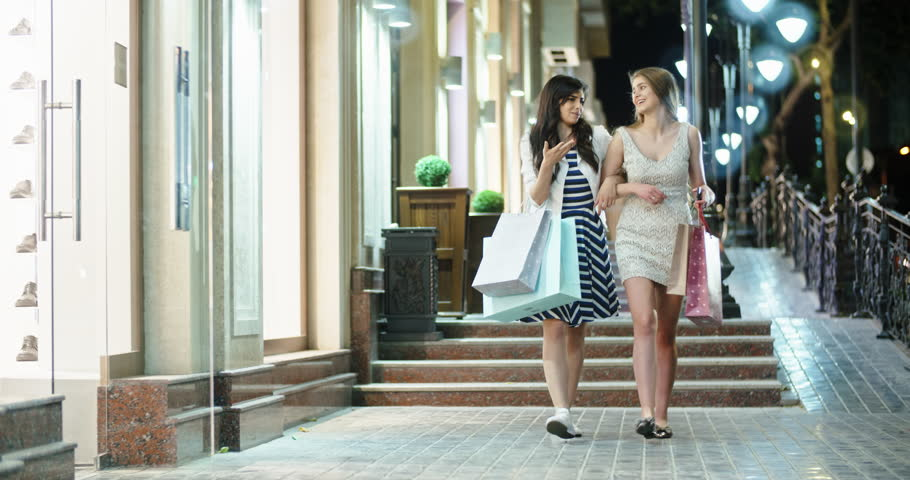 Two girls walking down broadway near shopping centers with bags in hands, then female friend joins them. Friends chatting and smiling 4k | Shutterstock HD Video #1015879915