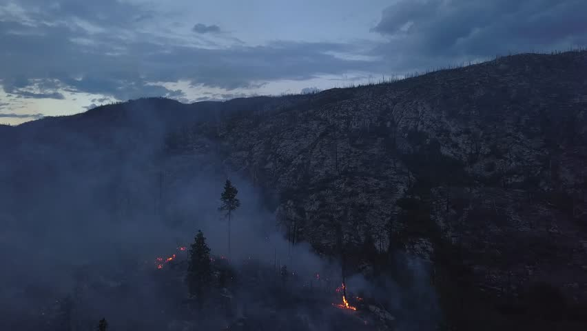 Kelowna BC Wildfire burning and flames from above in unique drone perspective.Rare view onto forest fire at twilight or dawn. Flames, glow, blaze and smoke over dead woods and trees.
