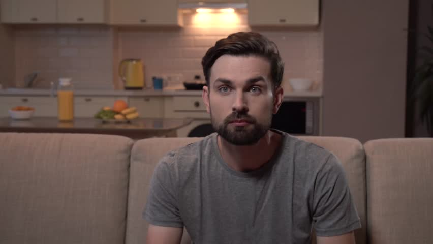 Bearded guy is watching TV. He is strained. Man eats popcorn and stretches his hand. He is worry. | Shutterstock HD Video #1015895686
