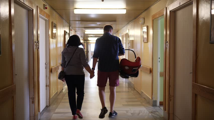 Parents with newborn baby in a car chair leavin the maternity hospital walk down the hall Royalty-Free Stock Footage #1015896181