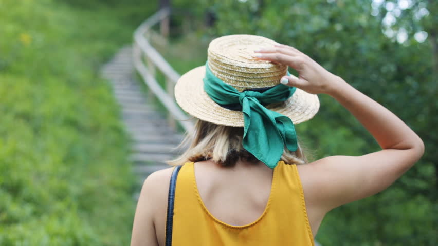 Nice young Caucasian woman wearing yellow t-shirt walking up the stairs. Slavic girl touching hat. Outdoors. Summertime. Back.