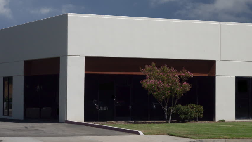 The front exterior of a small, generic office building is shown during a sunny day.