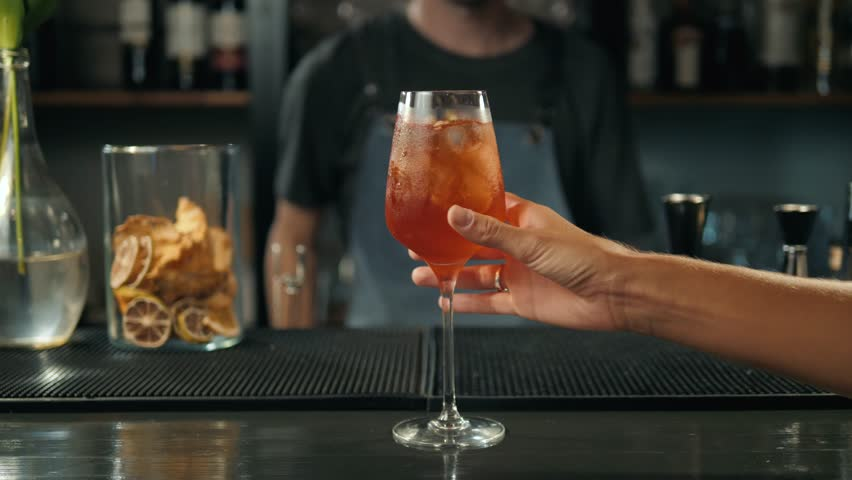 Woman hands toasting with aperol spritz cocktails, woman in bar take alcohol from bartender