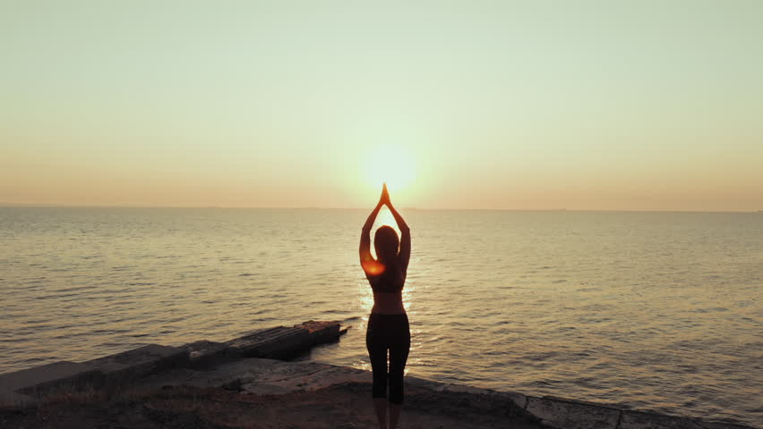 Silhouette of woman practicing yoga on hill over sea at sunset. Meditation. Flexibility workout at nature background. Drone amazing aerial view. Vriksasana. Pose of tree   Shutterstock HD Video #1015915753