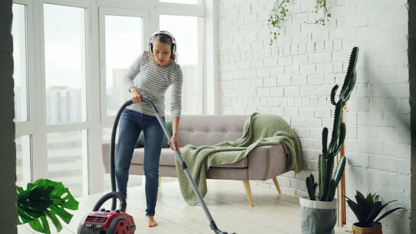 Cheerful blond housewife is using vacuum cleaner during routine clean-up at home, listening to music through headphones, singing and dancing. Technology and people concept. #1015918777