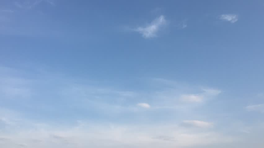 White clouds disappear in the hot sun on blue sky. Loop features time lapse motion clouds backed by a beautiful blue sky. Time-lapse motion clouds blue sky background and sun. #1015919386