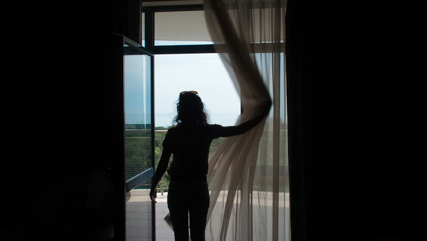 The girl opens the curtains. A woman in the room opens the curtains and goes out onto the terrace. | Shutterstock HD Video #1015919605