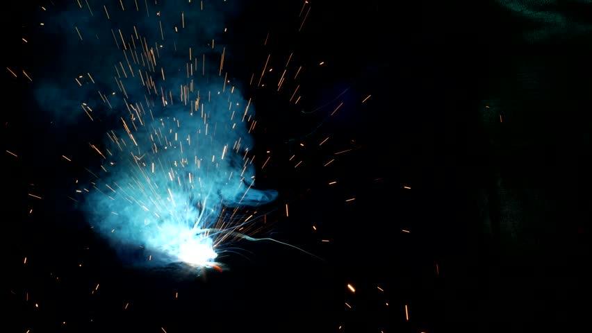 Welder welds a metal part, a lot of sparks and smoke, close-up, welding, close-up, spark | Shutterstock HD Video #1015922164