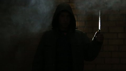 Teen in the hood in a closed dark room with brick wall