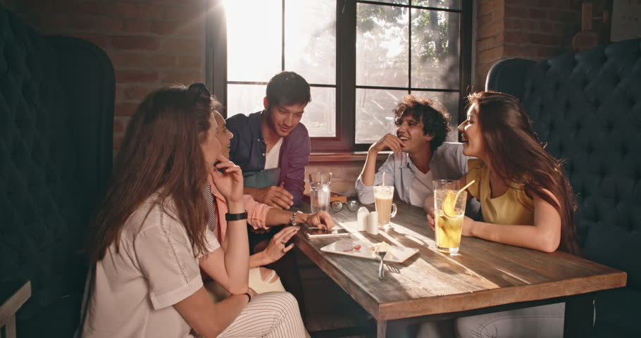 Five multiethnic friends sitting at table in cafe, talking, cheering, telling each other stories closeup 4k #1015963543