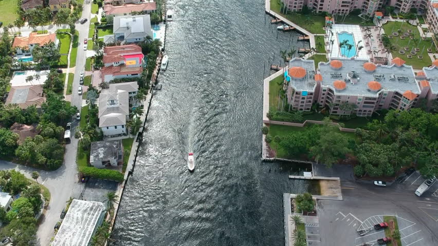 Drone shot down the many waterways in Boca Raton, Florida with luxury homes on either side.