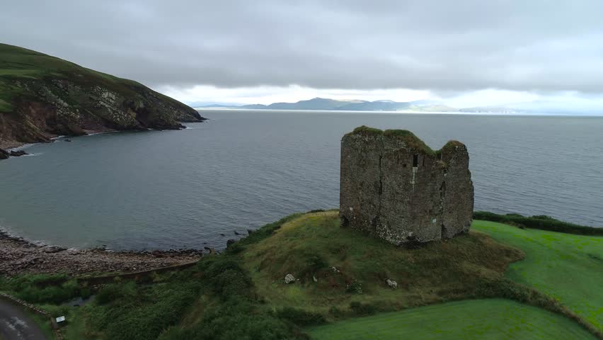 Aerial view of the Minard Castle situated on the rocky beach of the Dingle Peninsula with views across the Irish Sea in Kerry county, Ireland. 4K drone video. | Shutterstock HD Video #1015980397