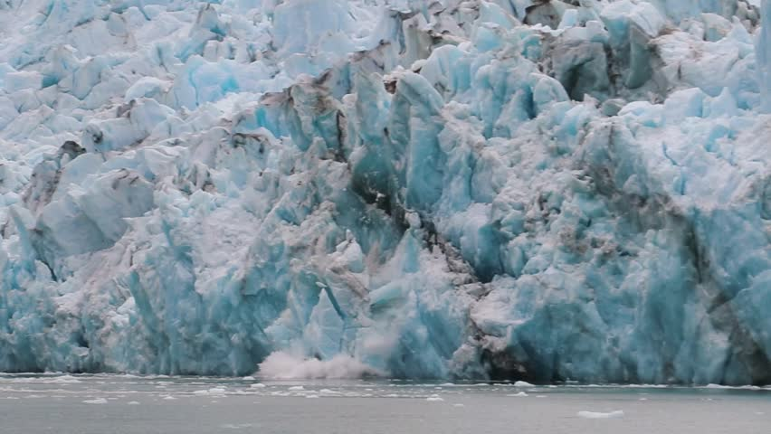 Slow motion, medium wide view of Dawes Glacier calving. Large chunks of jagged blue ice break from the face of the glacier and fall into the cold water of the fjord to form icebergs.