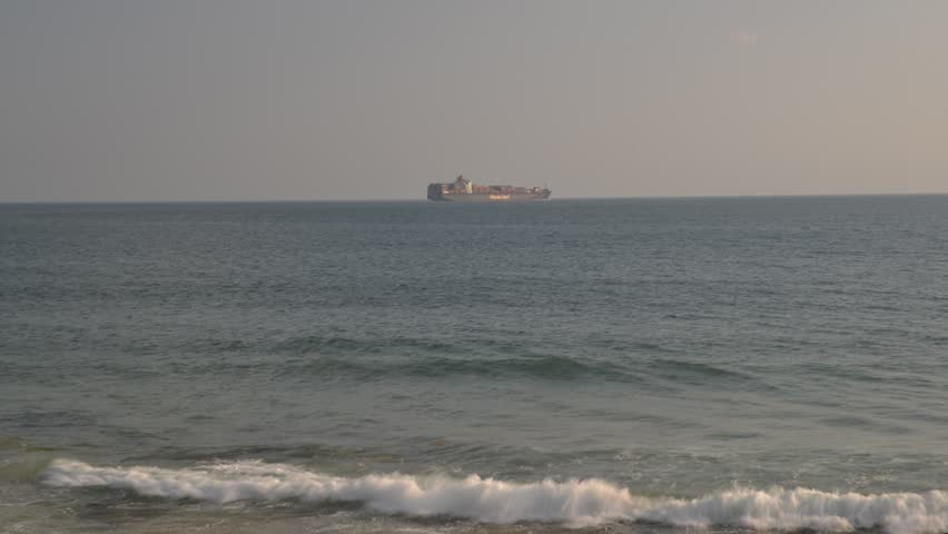 Carcavelos, Portugal - Sept 5, 2018: Time lapse of large, ocean-going oil tanker ship with containers belonging to Hapag Lloyd as seen from the Portuguese coast