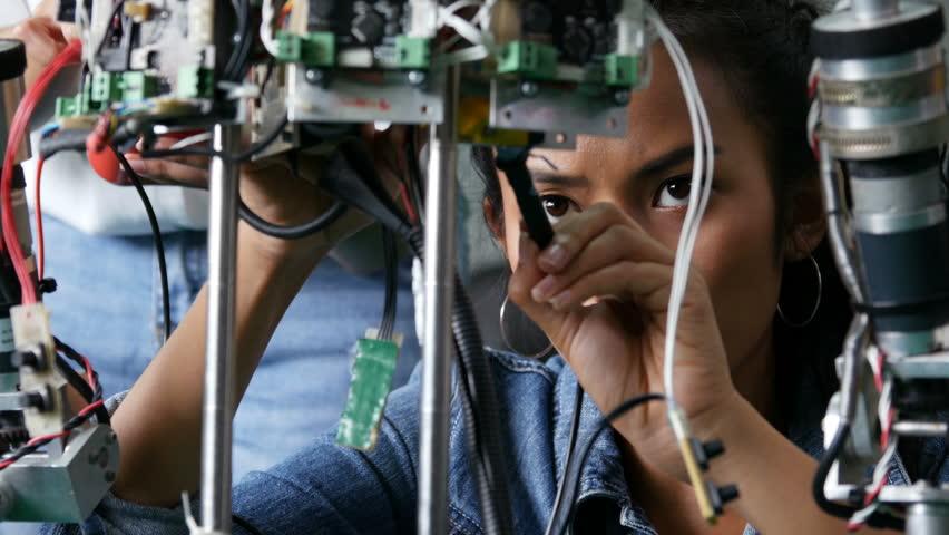 Female engineer fixing robot in workshop. Assistance help female engineer to fix robot. 4k resolution.