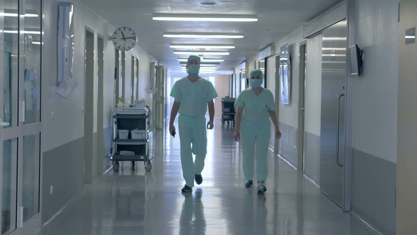 A male and a female surgeons are walking along the corridor of the clinic | Shutterstock HD Video #1015996141