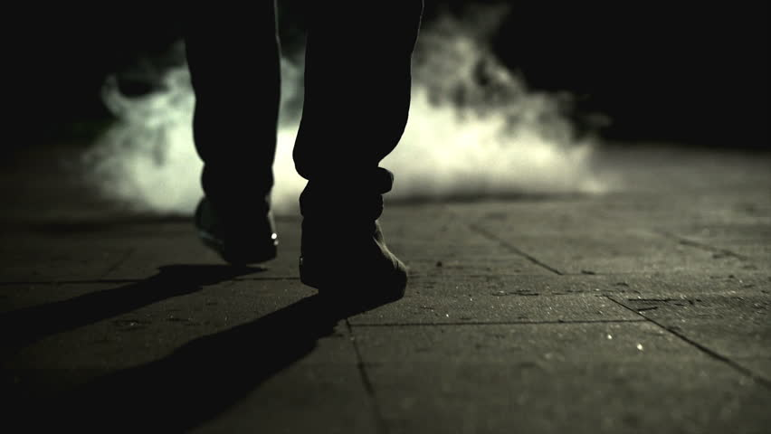 The legs of a man walking near the cloud of a smoke. slow motion