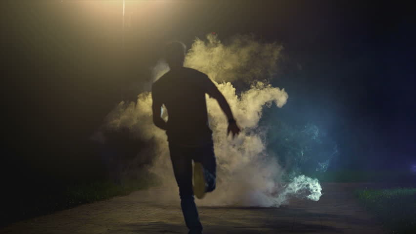 The man running in the cloud of smoke on the dark background, slow motion