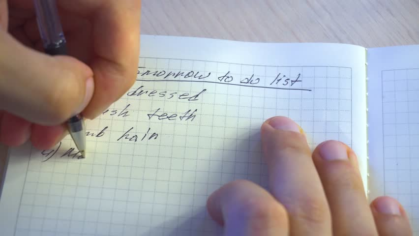 The guy writes himself a to do list of things to do in the morning Royalty-Free Stock Footage #1016001016