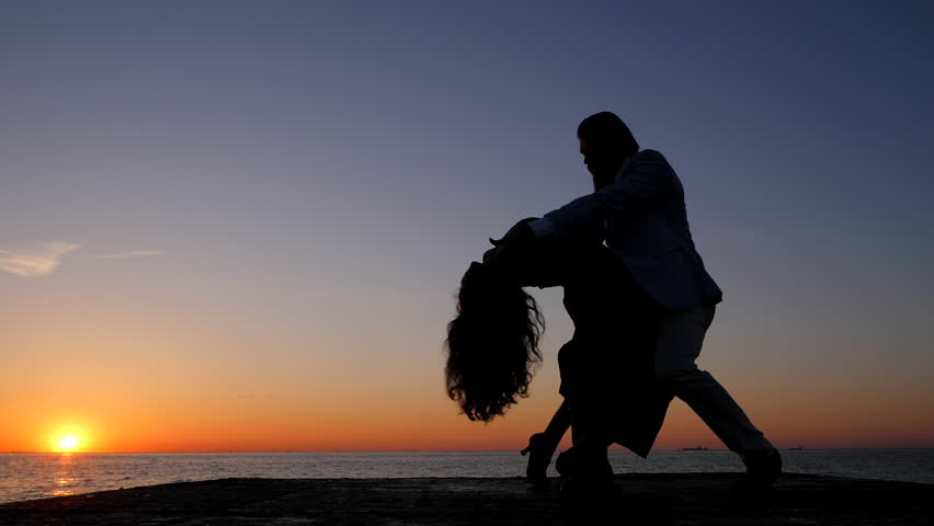 Silhouettes of young spanish couple against sunset sea background. Man and woman dancing latin american sensual dance: bachata, salsa or kizomba. Slow motion