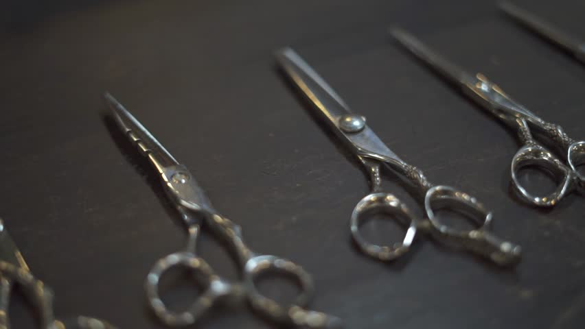 Hairdressing scissors and barber accessories in hair salon close up. Professional tools for haircut in barber shop. Hairdressing concept