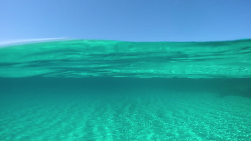 SLOW MOTION, HALF UNDERWATER: Picturesque view from the turquoise ocean of the distant island in the sunny Mediterranean. Cinematic half half of crystal clear sea and stunning Sardinia on a sunny day.
